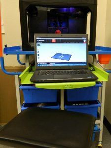 A 3D printer and laptop sit on a desk.