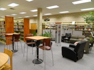 A view of the adult area at the Pearsall Public Library, including seating, plants, and shelves.